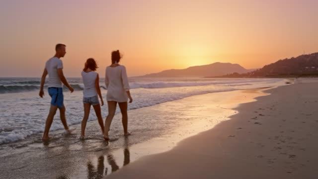 stockvideo's en b-roll-footage met man en vrouw bij zonsondergang op het strand met hun dochter lopend en pratend - spanje