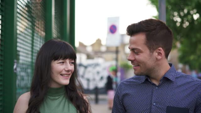vidéos et rushes de ts - man and woman walking, talking, smiling and enjoying each others company! - plan en travelling