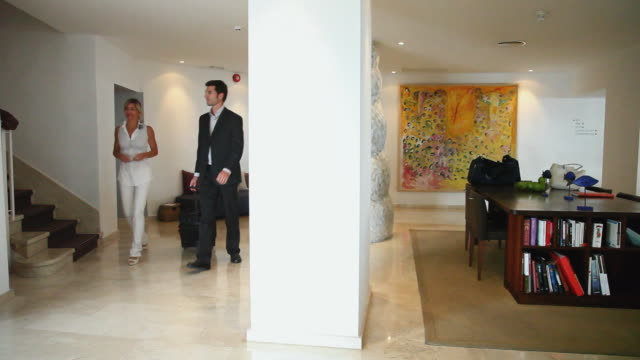 vídeos y material grabado en eventos de stock de ws pan man and woman walking through hotel lobby, waving to concierge / golf de son termes, bunyola, mallorca, baleares, spain - sala de espera edificio público
