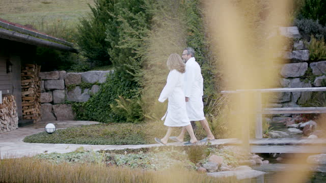 man and woman walking towards a sauna in towels near a pond - bathrobe stock videos & royalty-free footage