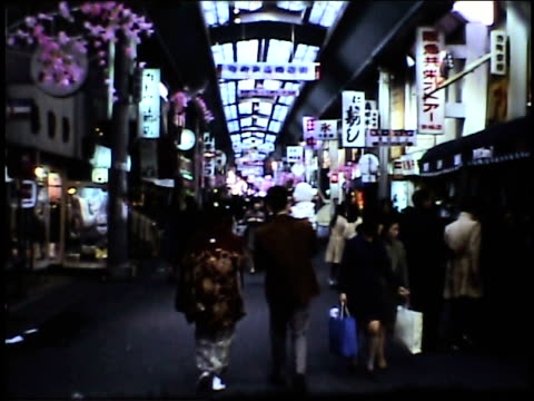 / man and woman walking with baby in shopping area. japanese shopping district on january 01, 1973 in japan - home movie stock videos & royalty-free footage