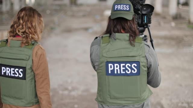 stockvideo's en b-roll-footage met de oorlogspers van de man en van de vrouw in oorlogsstreek - journalisme