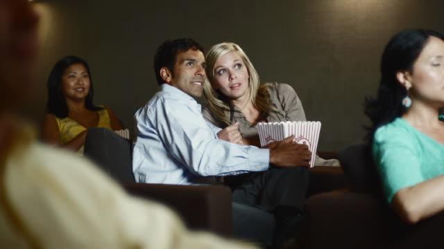 stockvideo's en b-roll-footage met ms man and woman watching scary movie in theater eating popcorn / bellevue, washington, usa - tanden op elkaar klemmen
