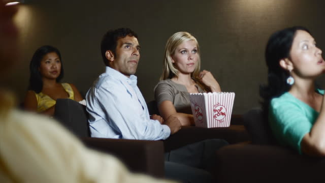 ms man and woman watching scary movie in theater eating popcorn / bellevue, washington, usa - popcorn stock-videos und b-roll-filmmaterial