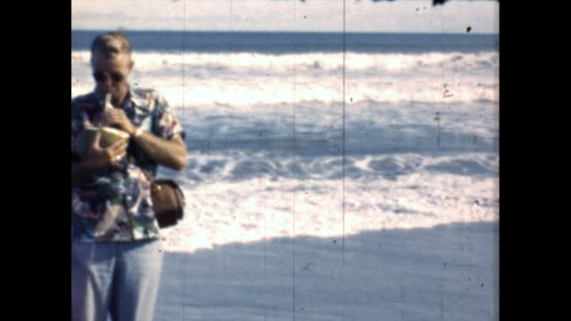"""vídeos de stock e filmes b-roll de man and woman wearing """"aloha"""" shirts and sunglasses walk on beach and drink coconut water from a coconut shell. - aloha"""
