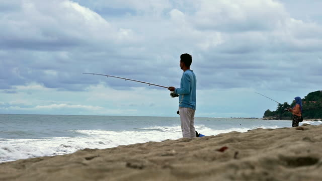 man and woman with fishing rods fishing on the beach - ross sea stock videos & royalty-free footage
