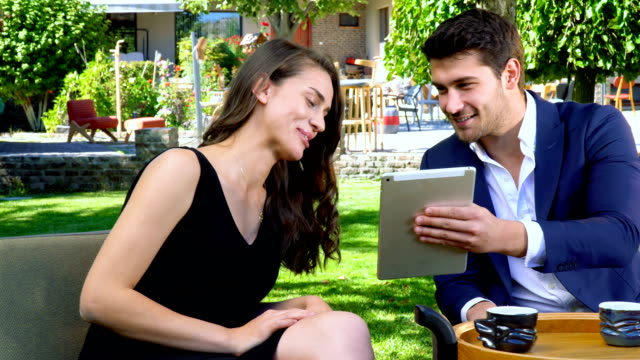 vídeos de stock e filmes b-roll de man and woman with formal clothes sitting and drinking coffee in garden - formal garden