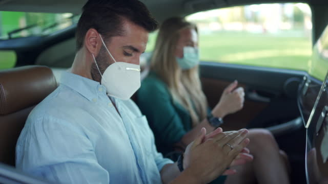 man and woman with protective face masks, disinfecting hands with antiseptic while sitting at back seat at crowdsourced taxi - taxi stock videos & royalty-free footage