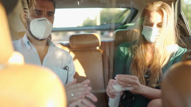 vídeos y material grabado en eventos de stock de hombre y mujer con máscaras protectoras para la cara, desinfectando las manos con antiséptico mientras están sentados en el asiento trasero en el taxi de crowdsourced - asiento de atrás