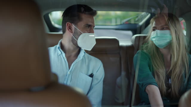 man and woman with protective face masks, sitting on back seat of crowdsourced taxi, talking and enjoying a ride - girlfriend stock videos & royalty-free footage