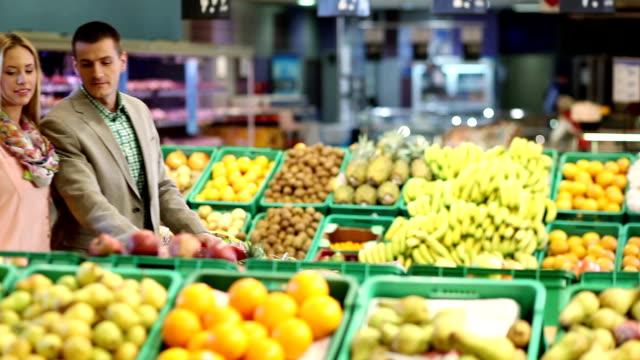 vídeos y material grabado en eventos de stock de hombre y mujer con carrito de frutas en supermercado contador - carrito de la compra