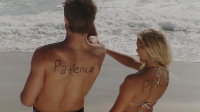 ms ha man and woman with words 'patience' and 'peace' written on back standing on beach, laguna beach, california, usa - laguna beach california stock videos & royalty-free footage
