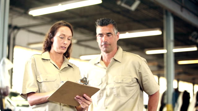 Man and woman working for trucking company, clipboard