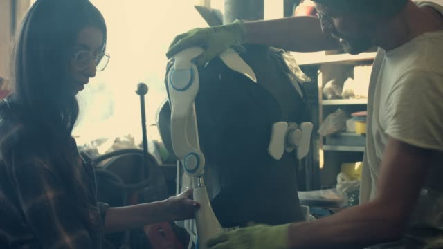 man and woman working in workshop. project exoskeleton - man and machine stock videos & royalty-free footage