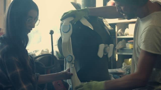 man och kvinna som arbetar i verkstad. projektet exoskelett - middle eastern ethnicity bildbanksvideor och videomaterial från bakom kulisserna