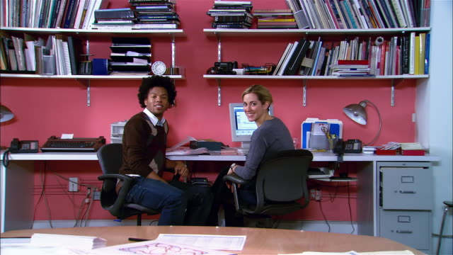 Man and woman working together at desk / swiveling around in chairs and smiling at camera / turning back around and resuming work