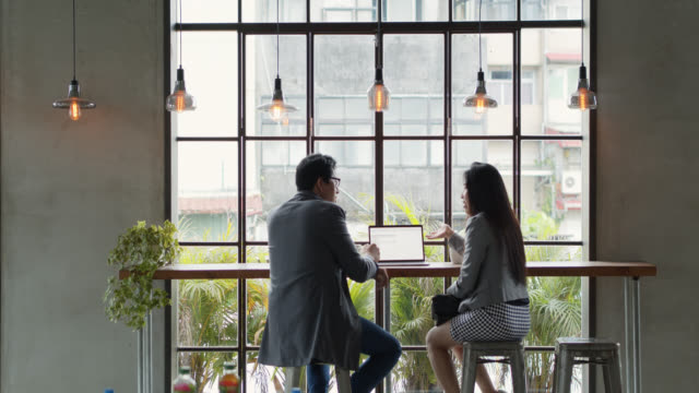 man and woman working together in cafe in taipei - asian colleague stock videos & royalty-free footage