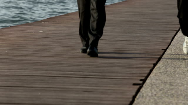 man and woman's feet walking on jetty above sea - pier stock videos & royalty-free footage