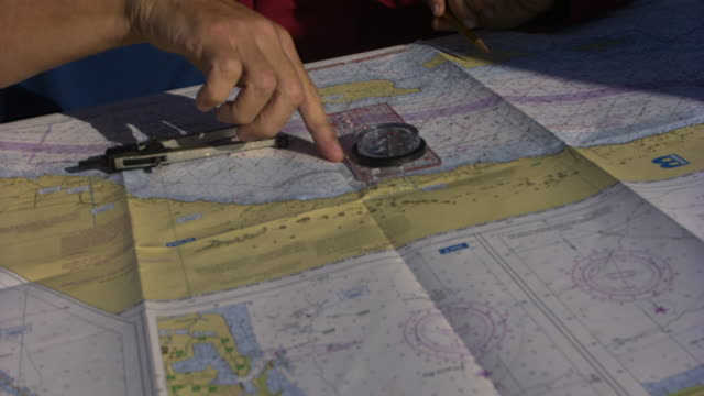 cu man and woman's hands pointing on map on yacht, santa barbara, california, usa - indicare video stock e b–roll