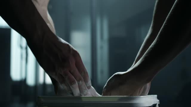 vídeos y material grabado en eventos de stock de hombre y mujeres marcar con tiza las manos antes de levantamiento de pesas en el gimnasio - magnesio