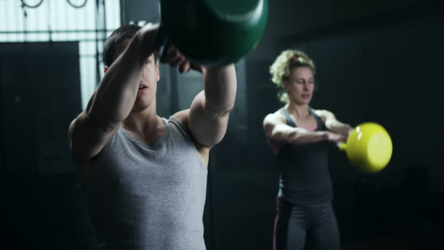 man and women doing exercise with kettlebell in gym - kettlebell stock videos & royalty-free footage