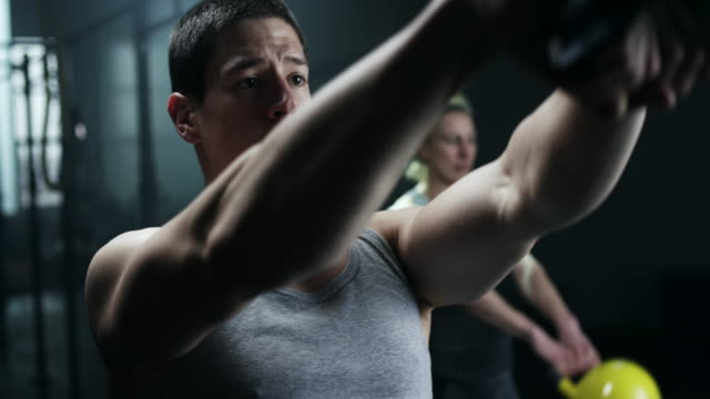 Man and women doing exercise with kettlebell in gym