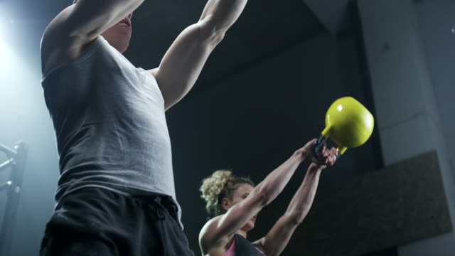 man and women doing exercise with kettlebell in gym - gym stock videos & royalty-free footage