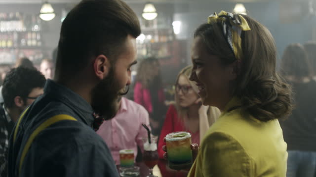 男性と女性カクテル バーでカクテルや笑を飲む - bar点の映像素材/bロール