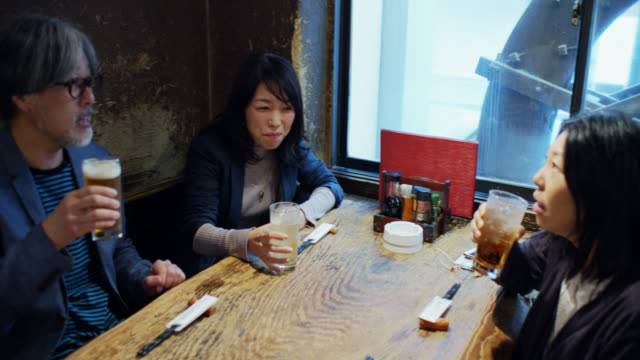 man and women drinking in tokyo bar - handheld - catering building stock videos & royalty-free footage