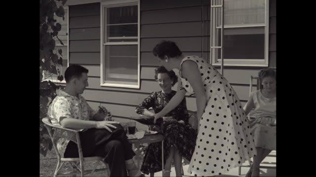 MS PAN Man and women sitting in veranda and enjoying, woman pouring drink into glass / United States