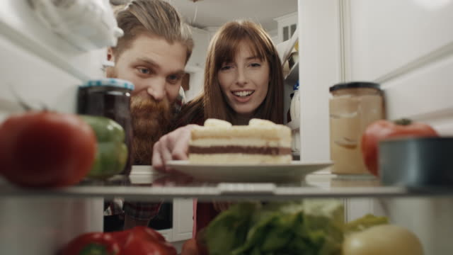 man and women taking cake from refrigerator - open refrigerator stock videos & royalty-free footage