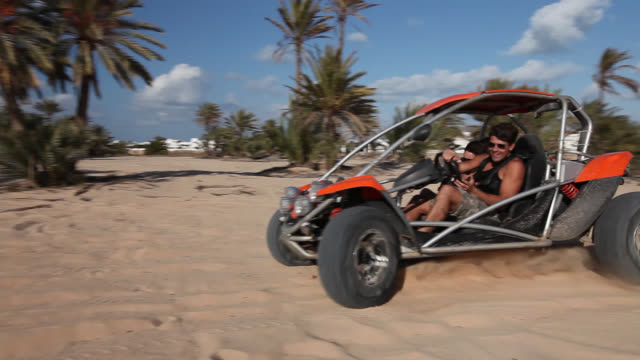 man and women with buggy in the desert - golf cart stock videos and b-roll footage