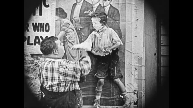 1919 Man (Fatty Arbuckle), annoyed, pastes the backside of a young boy and affixes him to the wall, after the boy retaliates, man spreads paste on his face