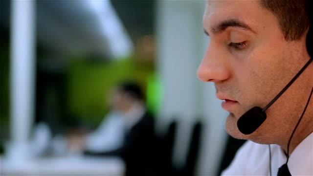 vídeos y material grabado en eventos de stock de hombre de contestar el teléfono en el servicio al cliente - centro de llamadas