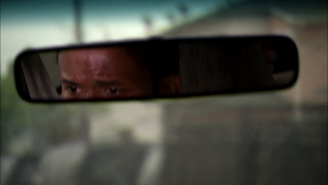 a man appears concerned as he watches his rear view mirror and drives in an urban neighborhood. - anxiety stock videos & royalty-free footage