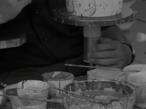 man applies paint detail to a bowl at the stavanger pottery workshop. 1959. - stavanger stock videos & royalty-free footage