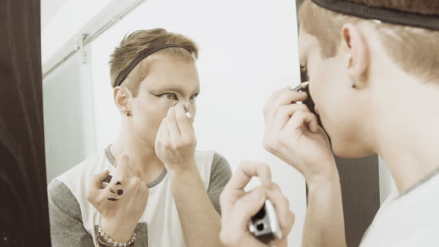 Man applying eye liner in mirror