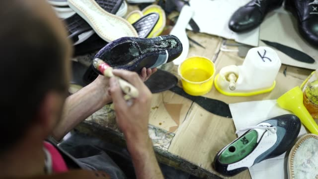 man applying glue on shoes in factory - glue stock videos & royalty-free footage