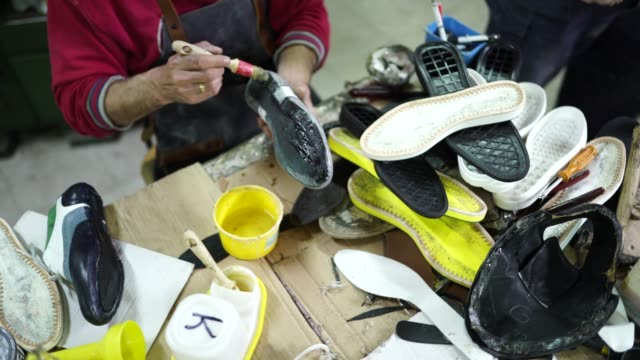 man applying glue on shoes in shoe factory - glue stock videos and b-roll footage