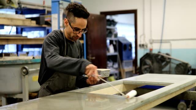uomo che applica sigillante sulla parte superiore della cucina in officina - sigillante video stock e b–roll