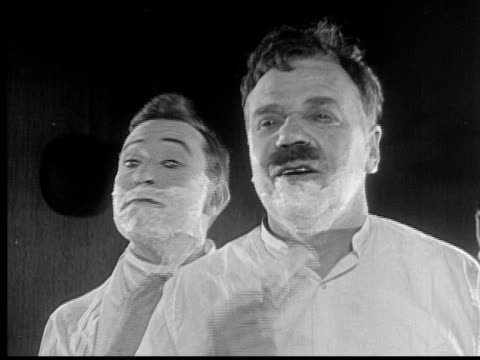 1924 b/w cu man (harry langdon) applying shaving cream on his face next to another man who looks back at him strangely / usa - moustache stock videos & royalty-free footage