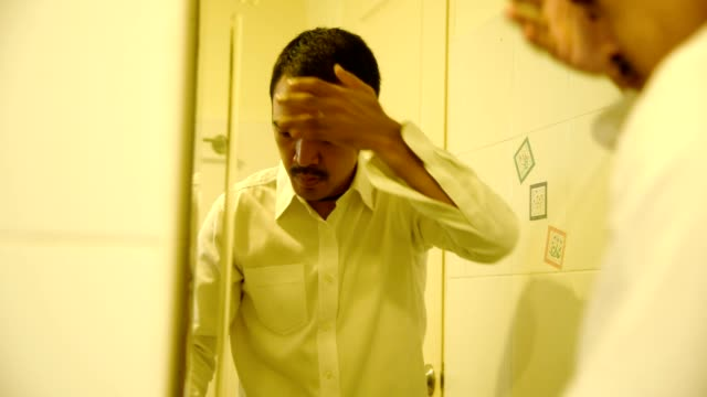 A man applying spray lotion for alopecia and hair loss treatment in the toilet.