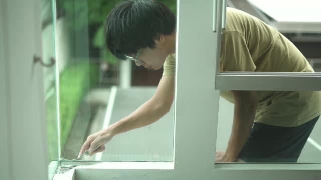 man applying the silicone sealant on window glass - sigillante video stock e b–roll