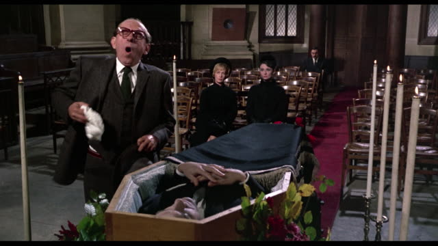 1963 Man (Ned Glass) approaches corpse at funeral and begins sneezing before walking away