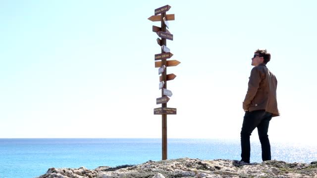 vídeos de stock, filmes e b-roll de homem abordagens multidirecional placa acima do mar - sinal