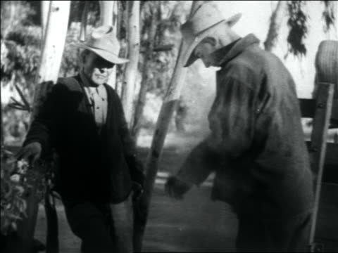 vidéos et rushes de b/w 1936 man approaches other man starts brushing dust off clothing / migrant workers - 1936