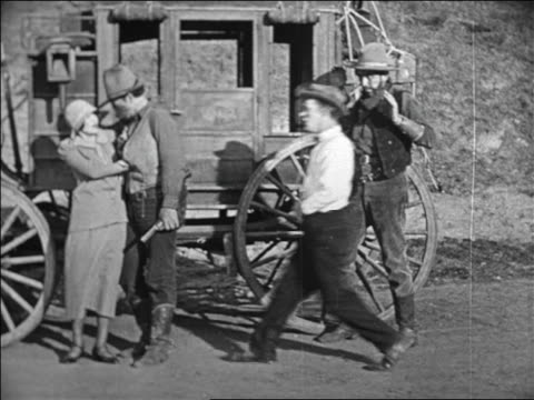 b/w 1924 man approaching robber accosting woman in stagecoach holdup / feature - neunzehntes jahrhundert stock-videos und b-roll-filmmaterial