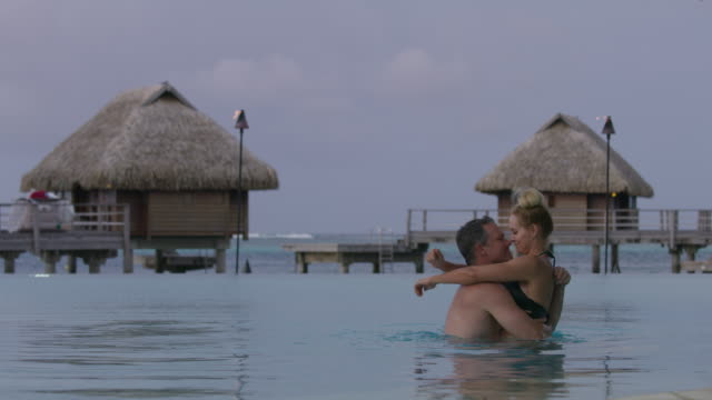 man approaching woman in ocean then hugging and kissing in tahiti / moorea, french polynesia - moorea stock videos and b-roll footage