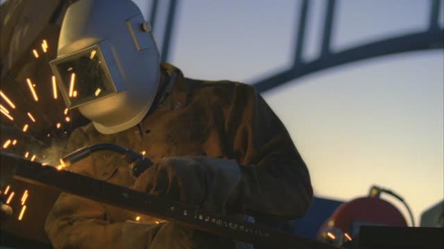 MS Man arc welding next to truck beside under construction bridge at Hoover dam / Mojave, California, USA