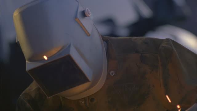 vídeos de stock, filmes e b-roll de cu man arc welding next to truck / boulder city, nevada, usa - boulder city